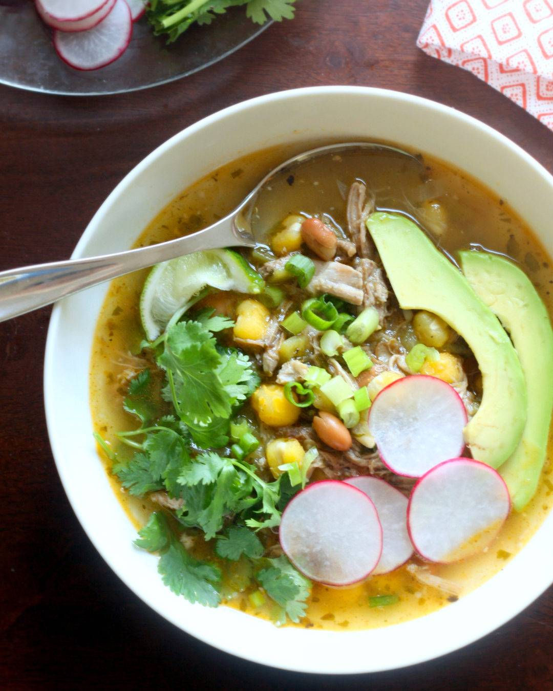 Bowl of Pork Posole Soup with cilantro, avocado, and radish garnishes