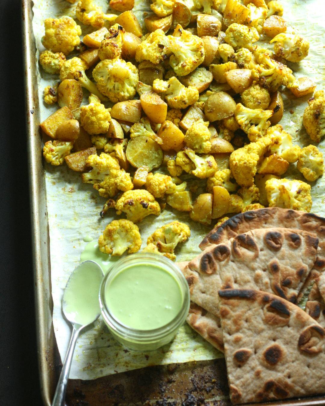 Sheetpan with roasted cauliflower and potatoes, grilled naan, and cilantro yogurt sauce