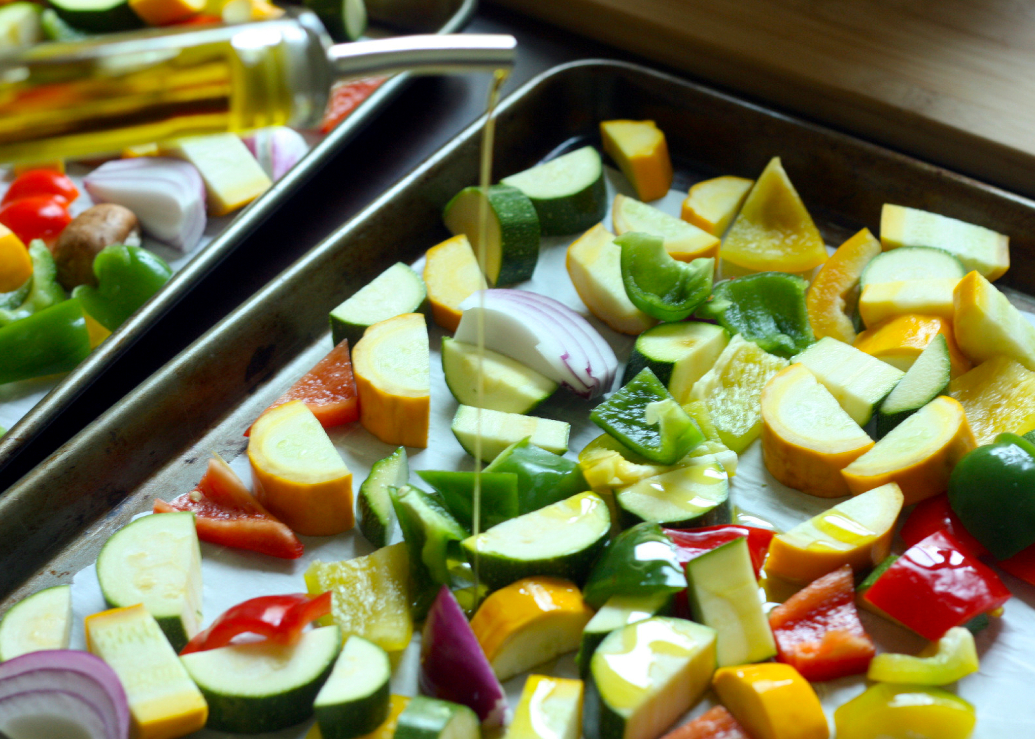 Pouring olive oil over vegetables on a sheet pan