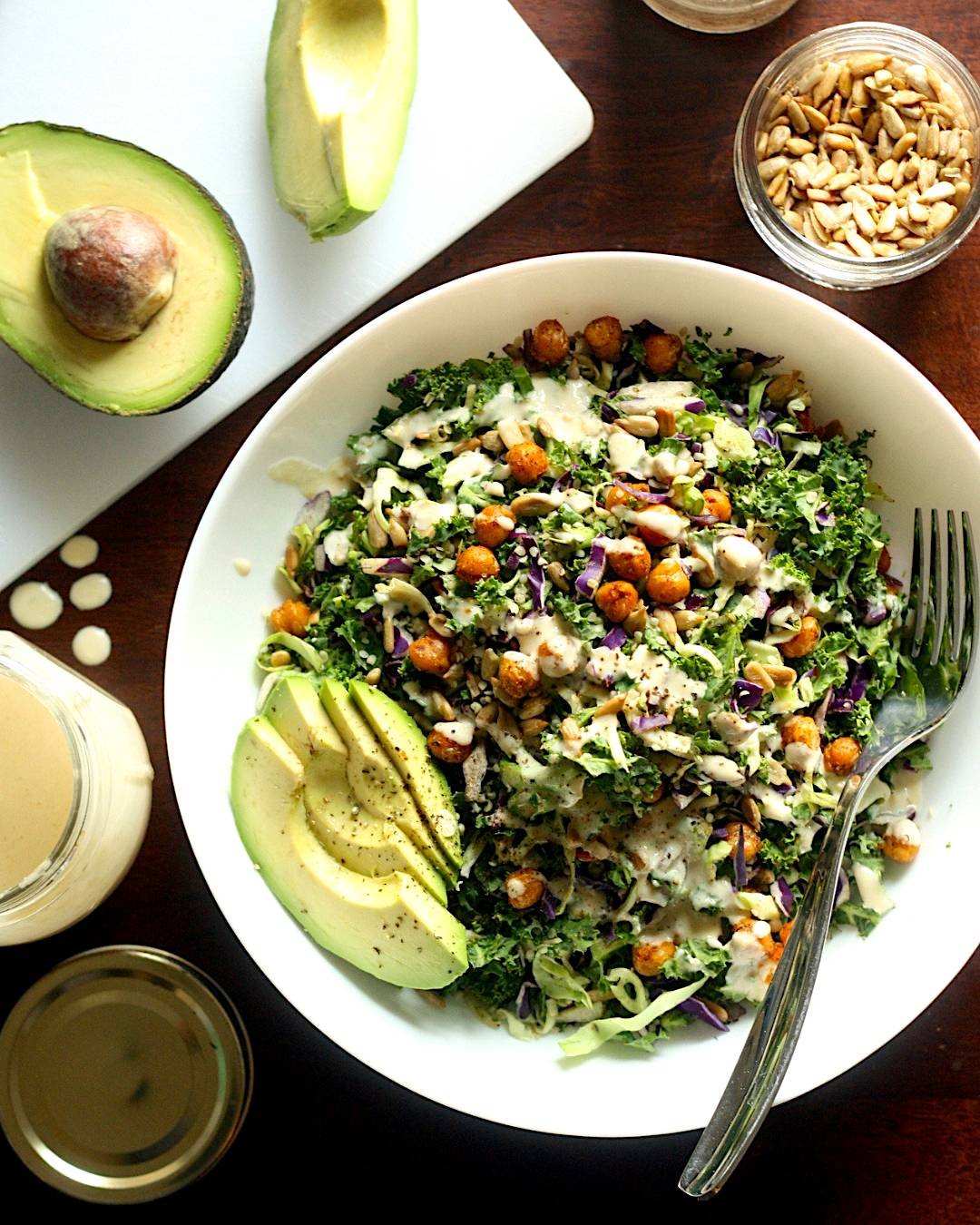 Large bowl containing chopped salad, chickpeas, sliced avocado and tahini dressing
