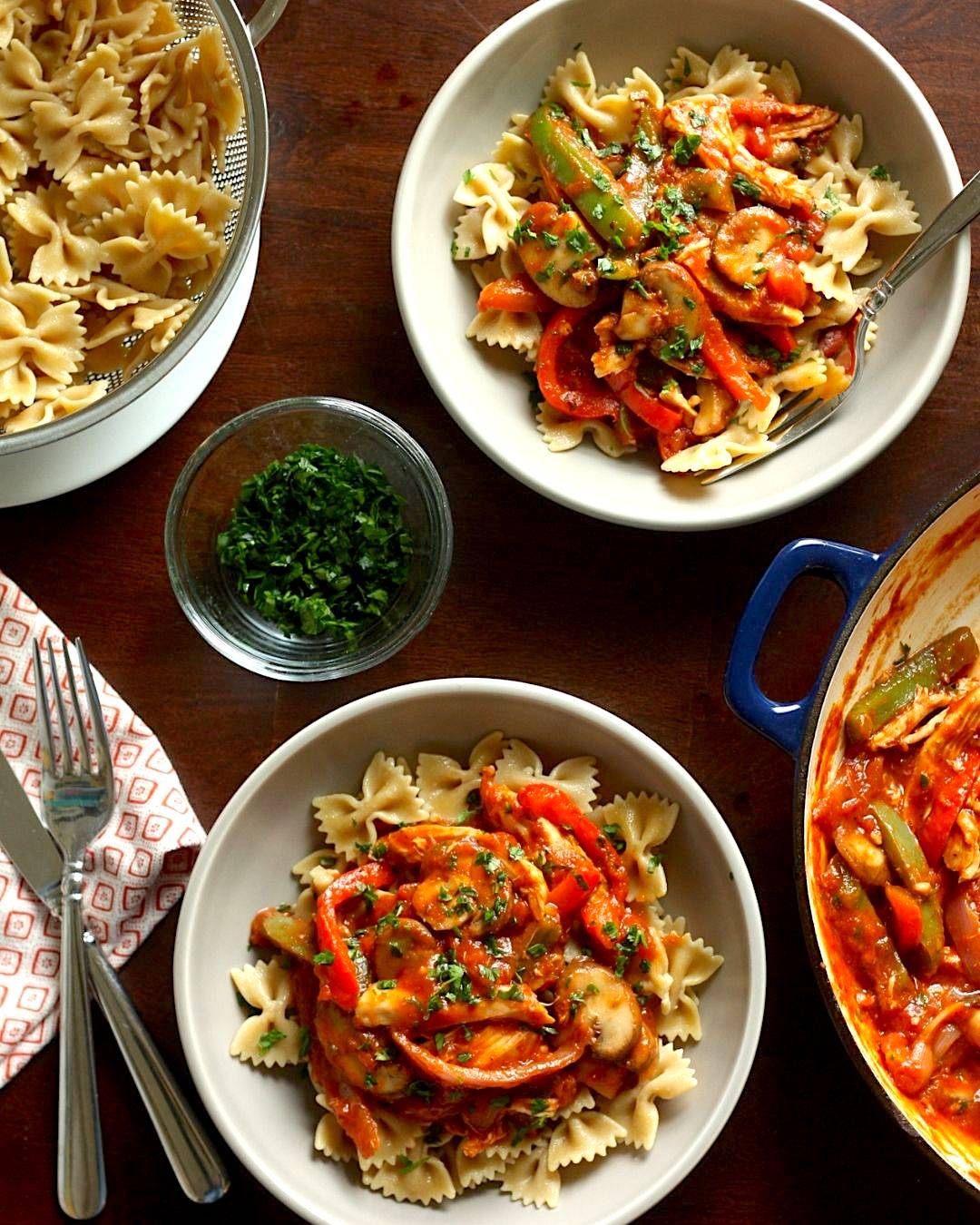 Dinner table setting with two bowls of chicken cacciatore pasta.