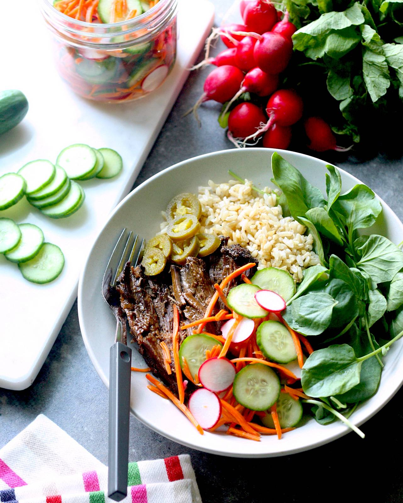 A tabletop display featuring a bowl with rice, greens and slow cooker beef roast with pickled vegetables, Banh Mi style.
