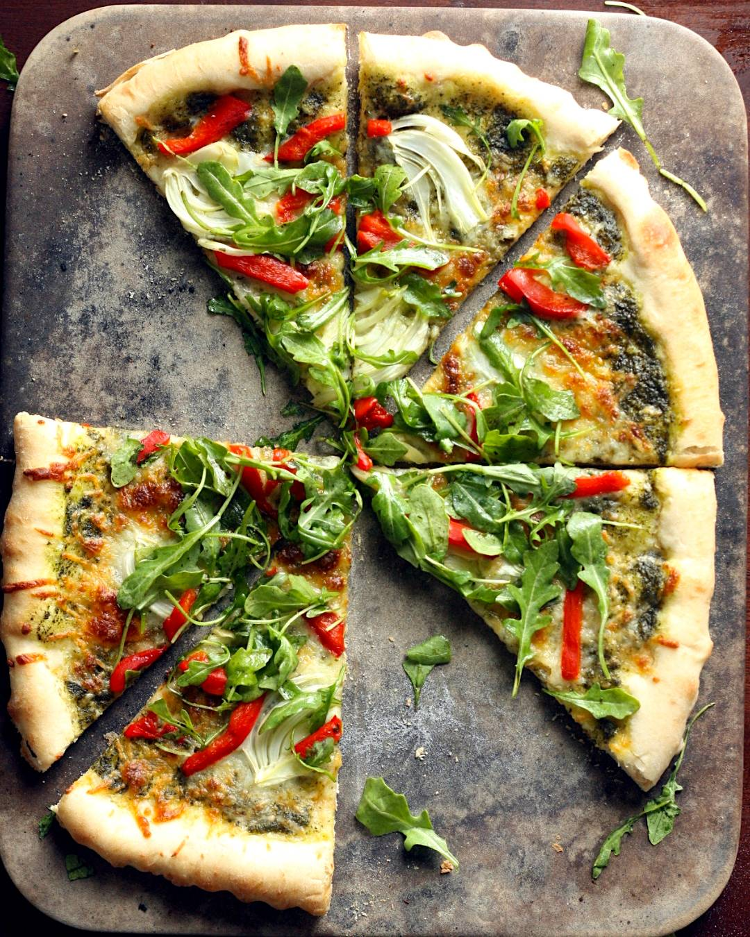 Store-bought pizza dough topped with pesto, roasted red peppers and fresh arugula