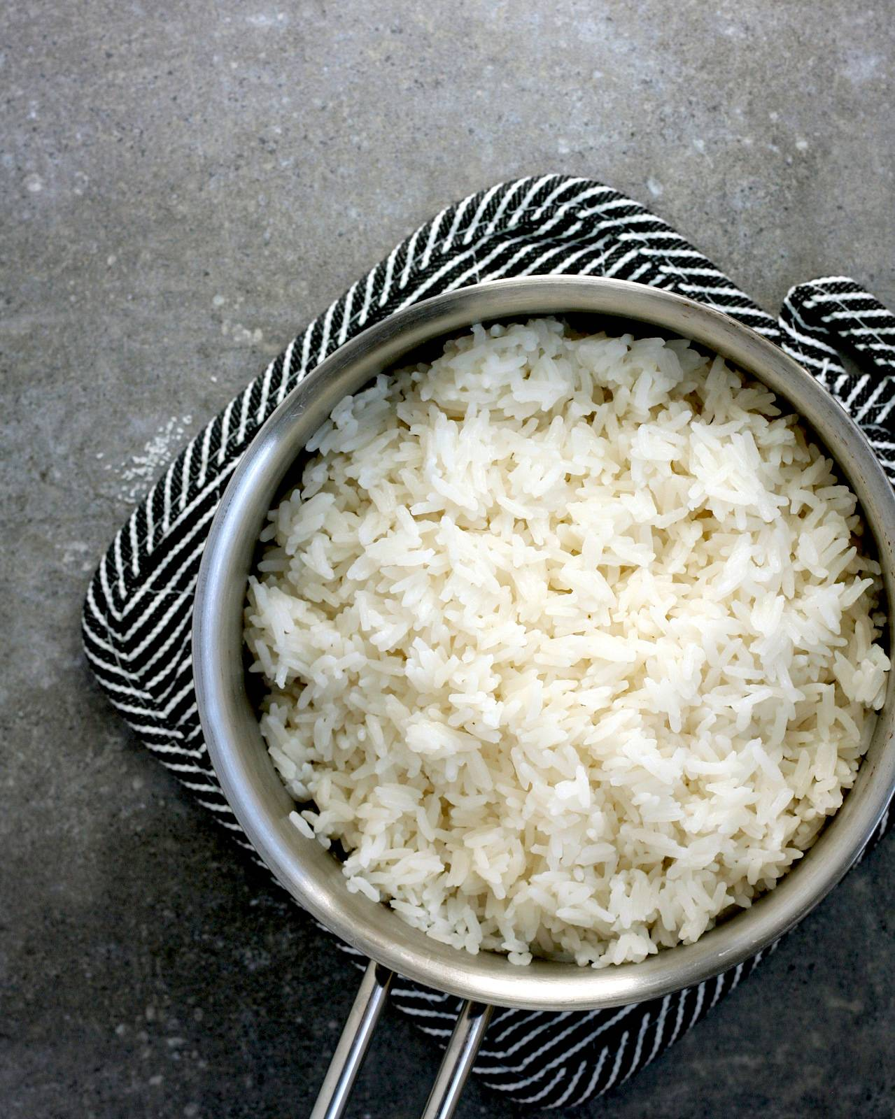 A small saucepan filled with fluffy coconut rice on a gray back drop