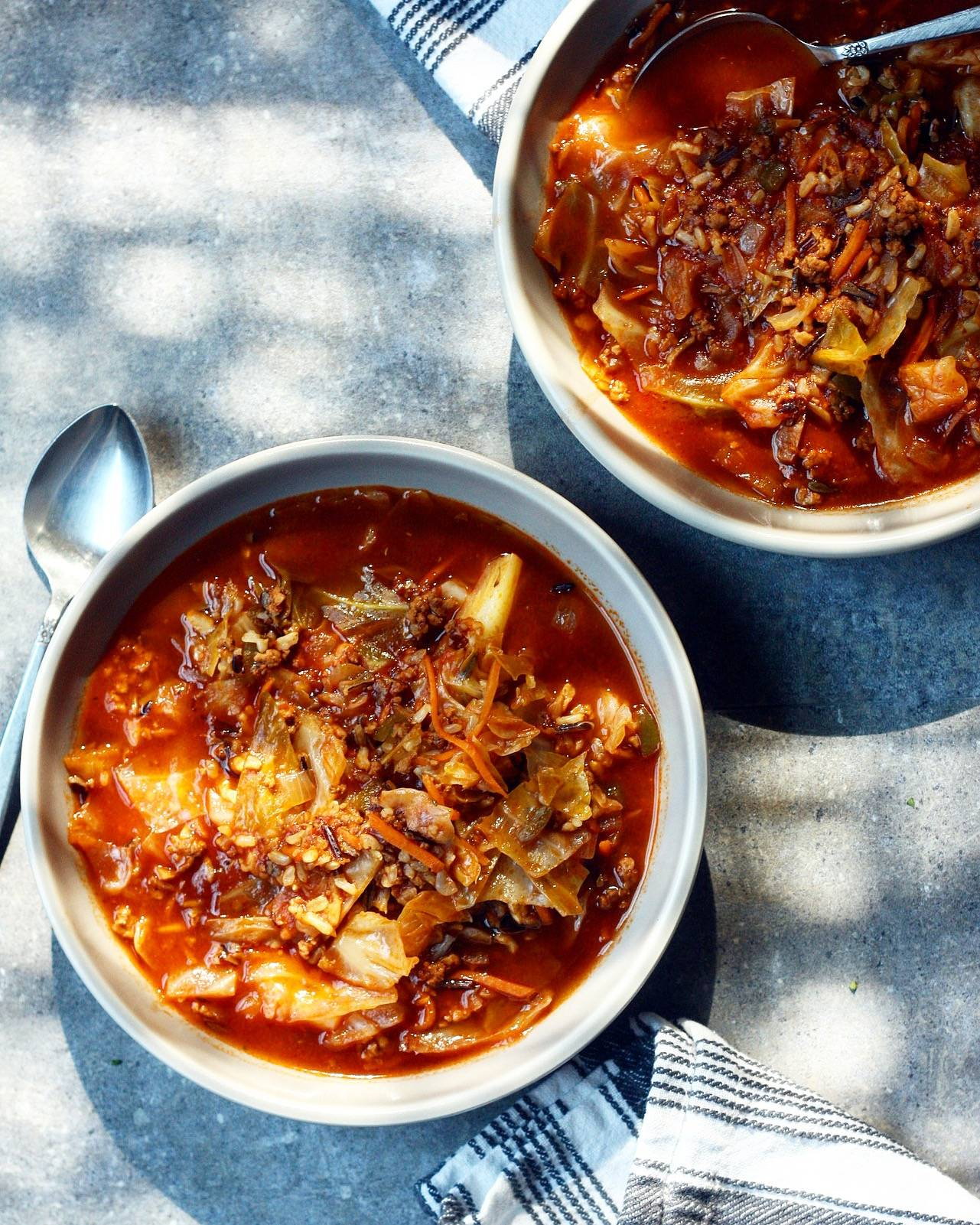 Two bowls of cabbage roll soup with wild rice on a gray backdrop