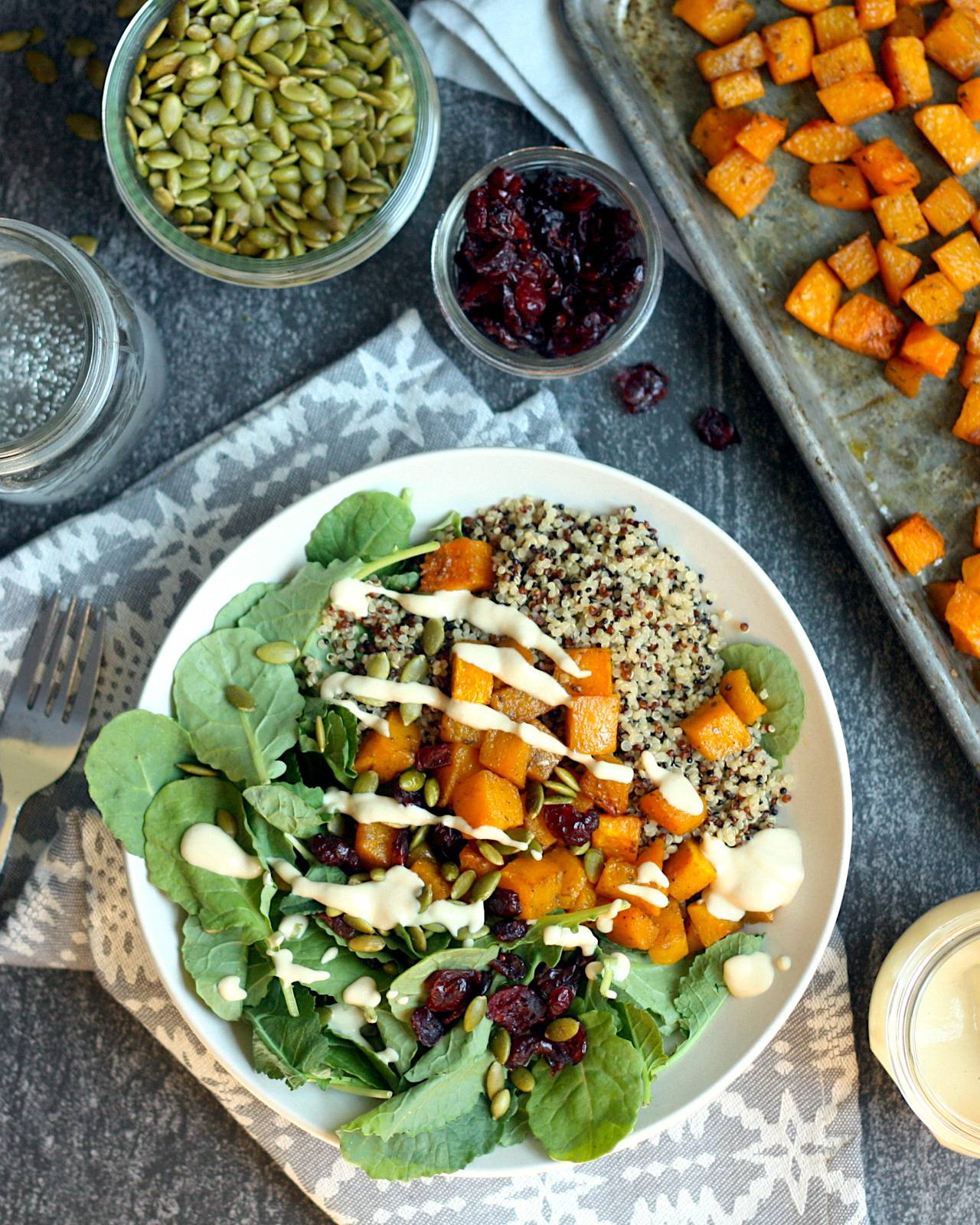 Quinoa grain bowls topped with roasted butternut squash, dried cranberries, toasted pepitas and maple-tahini dressing