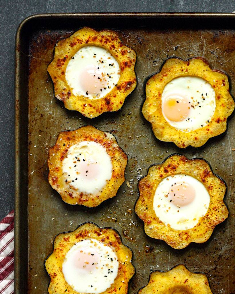Sheet pan with acorn squash rings around cooked eggs