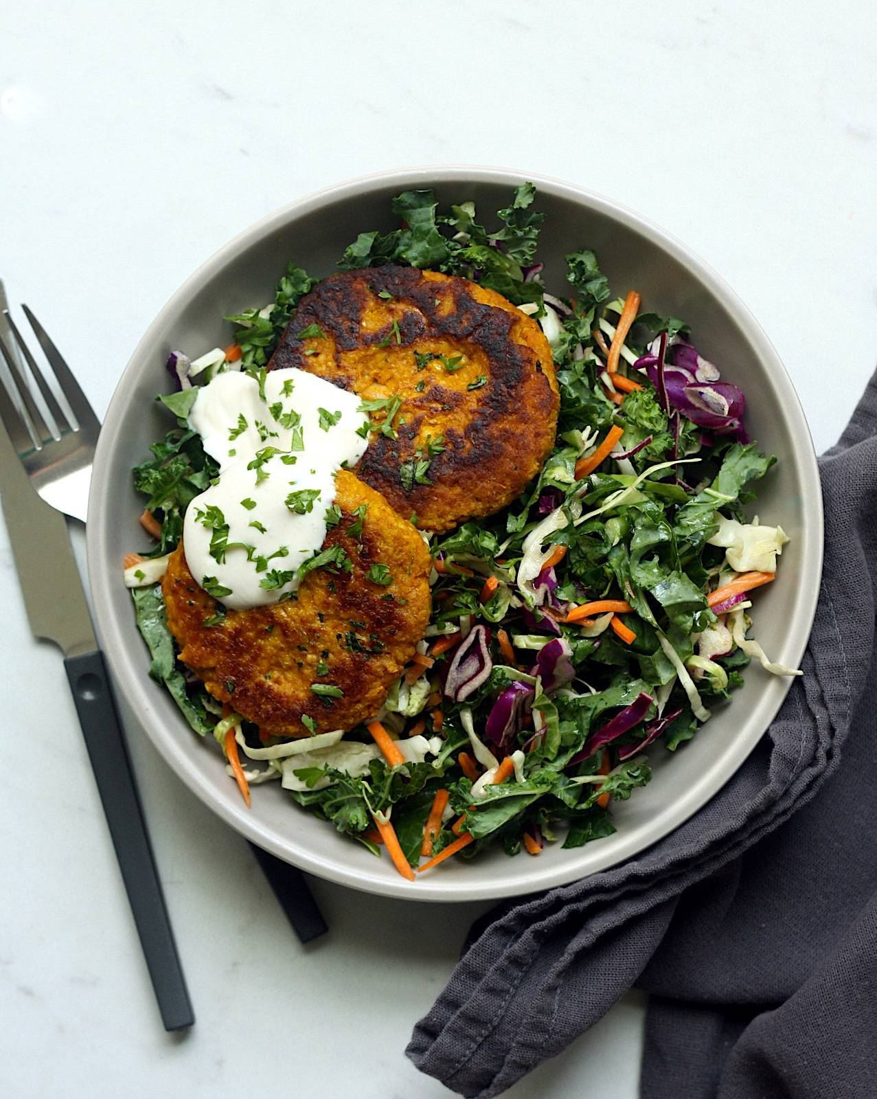 A large salad bowl with kale and greens topped with two curried pumpkin bean burgers and tahini sauce